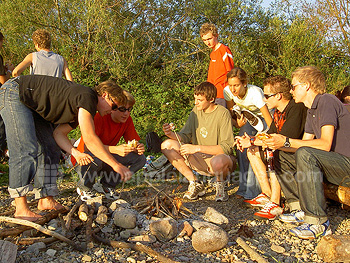 Young students barbeque by the lake